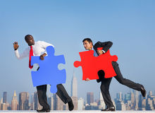 Two Businessmen in an Urban Scene with Puzzle Royalty Free Stock Image