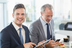 Two businessmen using digital tablet and mobile phone Stock Images