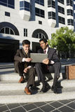 Two businessmen using laptop on pavement steps outside office block, smiling Stock Photo