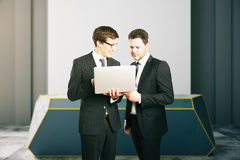 Two businessmen using laptop together Stock Photos