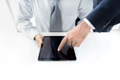 Two businessmen using tablet computer with one hand touching screen Royalty Free Stock Photography