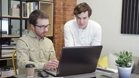 Two businessmen view information using wireless internet in the computer in office. One of them tells details business project showing in the monitor of laptop stock video footage