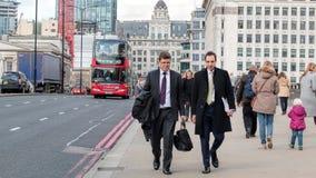 Two Businessmen Walking Across London Bridge. London, UK - March 31, 2016: Two Businessmen Walking Across London Bridge Royalty Free Stock Photography
