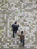 Two businessmen walking across a place and talking on the cellphone. Stock Photos
