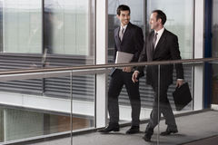 Two businessmen walking along in modern office building royalty free stock photo
