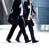 Two businessmen walking on the background of the office. Royalty Free Stock Photo
