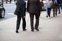 Two businessmen walking in the city. Two businessmen walking on the sidewalk in the busy city Royalty Free Stock Image