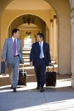 Two businessmen walking side by side in building arcade, luggage in tow, talking, front view Stock Images