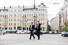 Two businessmen walking and talking on cell phone in city Stock Photos