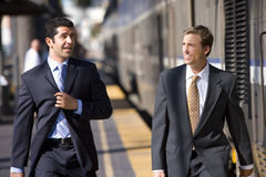 Two businessmen walking to train at train station Stock Photos