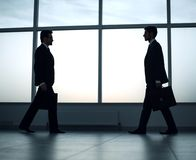Two businessmen are walking towards each other. Business concept royalty free stock image