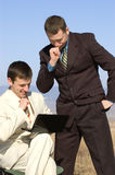 Two businessmen watching laptop. Sitting and standing businessmen watching laptop royalty free stock images
