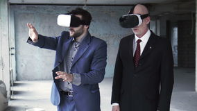 Two businessmen wearing on vr goggles and talking. Two businessmen in suits wearing on oculus rift and discussing something while gesturing stock video footage