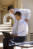 Two businessmen working in building arcade, man using laptop, side view royalty free stock image