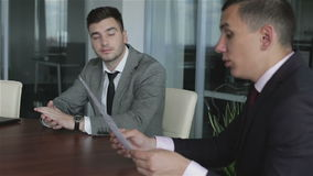 Two businessmen are working with documents in the office of the head. stock video footage