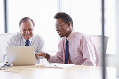Two Businessmen Working On Laptop At Boardroom Table Royalty Free Stock Images
