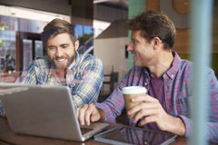 Two Businessmen Working On Laptop In Coffee Shop Stock Photo