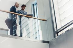 Two businessmen working at laptop. Low angle view of two businessmen looking at laptop while standing by a railing. Business people working together in office Stock Photography