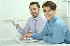 Two businessmen working on a laptop Stock Images