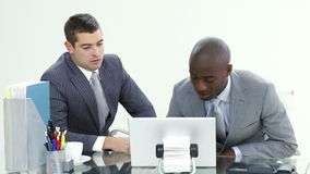 Two businessmen working with a laptop in office stock footage