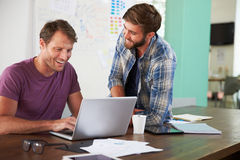 Two Businessmen Working On Laptop In Office Together Stock Photos