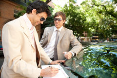 Businessmen meeting around car. Stock Photos