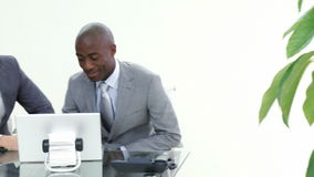 Two businessmen working in office together. Footage in high definition of AfroAmerican and caucasian businessmen working in office together stock footage