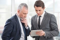 Two businessmen working on tablet computer Stock Image
