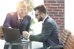 Two businessmen working together using laptop on business meeting in office. Two happy young businessmen working together using laptop on business meeting in Royalty Free Stock Image