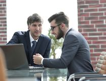 Two businessmen working together using laptop on business meeting in office. Two happy young businessmen working together using laptop on business meeting in Royalty Free Stock Photo