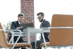 Two businessmen working together using laptop on business meeting in office. Two happy young businessmen working together using laptop on business meeting in Royalty Free Stock Photos