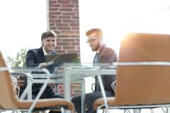 Two businessmen working together using laptop on business meeting in office. Two happy young businessmen working together using laptop on business meeting in Royalty Free Stock Images