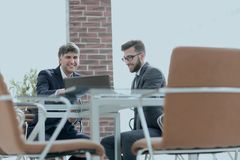 Two businessmen working together using laptop on business meeting in office. Two happy young businessmen working together using laptop on business meeting in Stock Images