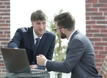 Two businessmen working together using laptop on business meeting in office. Two happy young businessmen working together using laptop on business meeting in Stock Image