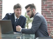 Two businessmen working together using laptop on business meeting in office. Two happy young businessmen working together using laptop on business meeting in Stock Photo