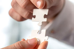 Two businesspeople fitting together puzzle pieces Stock Photo