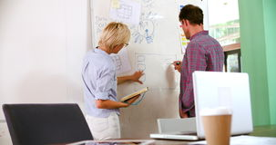 Two Businesspeople Having Brainstorming Meeting In Office. Businessman and businesswoman having brainstorming meeting in office and writing ideas on whiteboard stock video footage