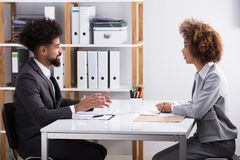 Two Businesspeople Having Conversation In Office. E View Of Two Young Businesspeople Having Conversation In Office stock image