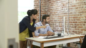 Two Businesspeople Having Meeting In Design Studio. Businessman sits at desk in modern office before being joined by female colleague to discuss paperwork.Shot stock footage