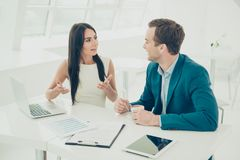 Two businesspeople having a meeting in a restaurant discussing t. Heir new strategy and drinking coffee Royalty Free Stock Image
