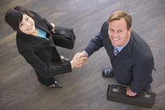 Two businesspeople indoors shaking hands smiling Royalty Free Stock Photos