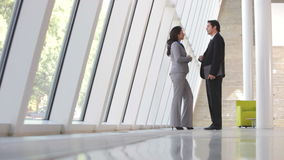 Two Businesspeople At Informal Meeting In Office. Businessman and businesswoman standing by window in modern office having informal meeting.Shot on Canon 5d Mk2 stock footage