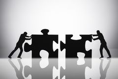 Two Businesspeople Joining Jigsaw Puzzle Pieces. Silhouette Of Two Businesspeople Joining Jigsaw Puzzle Pieces On Reflective Desk stock photos