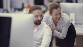 Two businesspeople are laughing from the joke of colleague. They`re looking outside the camera and smiling. Prores codec stock video