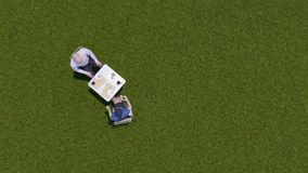 Two businesspeople at lunch on grass top view. Top view of two formally dressed businesspeople - man and woman sitting at table and talking during business lunch stock video footage