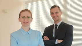 Two businesspeople man and woman are standing and smiling looking into the camera with approval in the office on a stock video