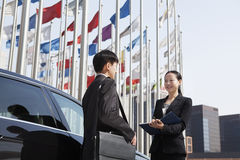 Two businesspeople meeting outdoors with flagpoles in background. Royalty Free Stock Photos