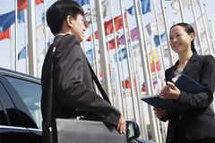 Two businesspeople meeting outdoors with flagpoles in background. Stock Images