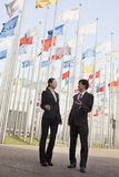 Two businesspeople meeting outdoors with flagpoles in background. Royalty Free Stock Image