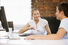 Two businesspeople in office talking and smiling.  stock image